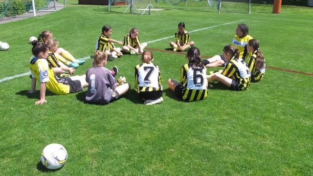 Mädchen sitzen im Fussballdress im Kreis auf dem Fussballfeld.