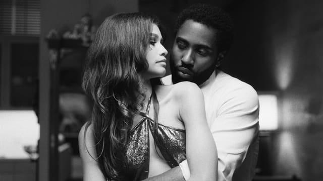 Szene aus einem Film: Ein Mann im Hemd umarmt eine Frau im Abendkleid von hinten. Sie schaut ihn über ihre Schulter an.