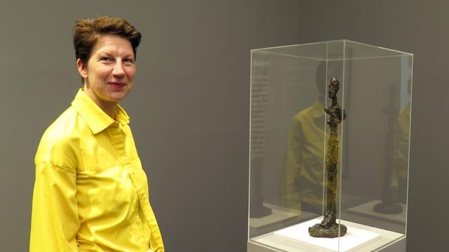Eine Frau steht neben einer Skulptur.