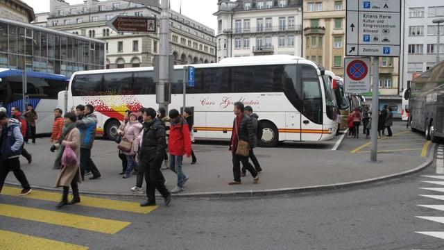 Touristen überqueren die Strasse beim Löwenplatz Luzern. Im Hintergrund sind Reisecars parkiert.