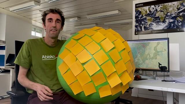 Ein Mann sitzt mit einem mit Post-It-Klebern vollgeklebten grossen grünen Gummiball vor dem Computer