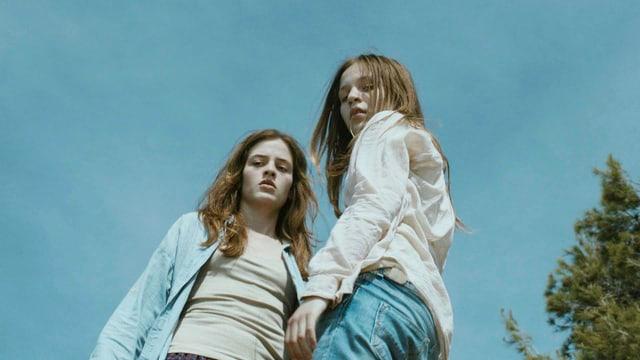 Zwei junge Mädchen schauen mit ernsten Gesichtern von oben in die Kamera.