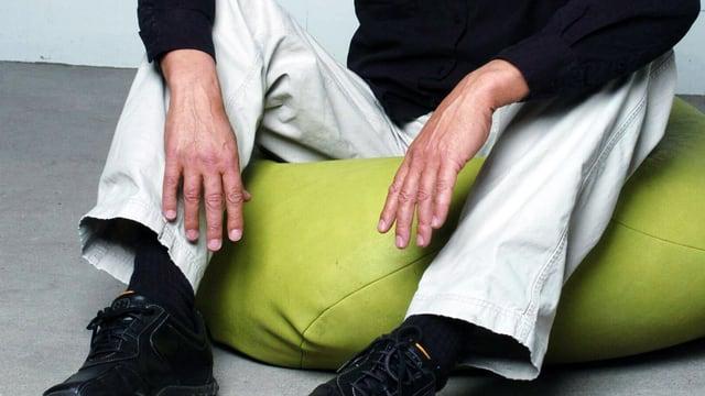 Mann sitzt auf einem besonders flauschigen Sitzkissen