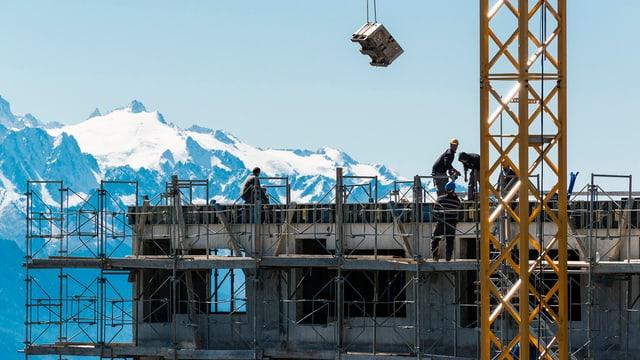 Ein Kran, eine Baustelle und Bauarbeiter. Im Hintergrund ein Bergmassiv.
