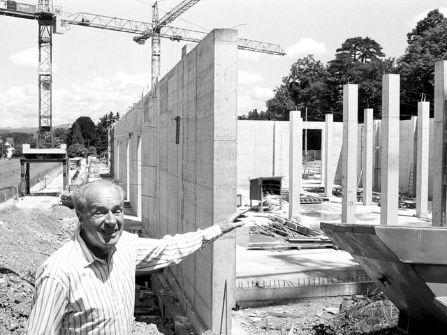 Ein Mann in gestreiftem Hemd zeigt lächelnd auf einen unfertigen Rohbau aus Beton, im Hintergrund Kräne.