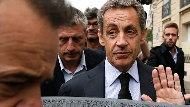Nicola Sarkozy umgeben von Männern grüsst mit der offenen Handlfäche Journalisten