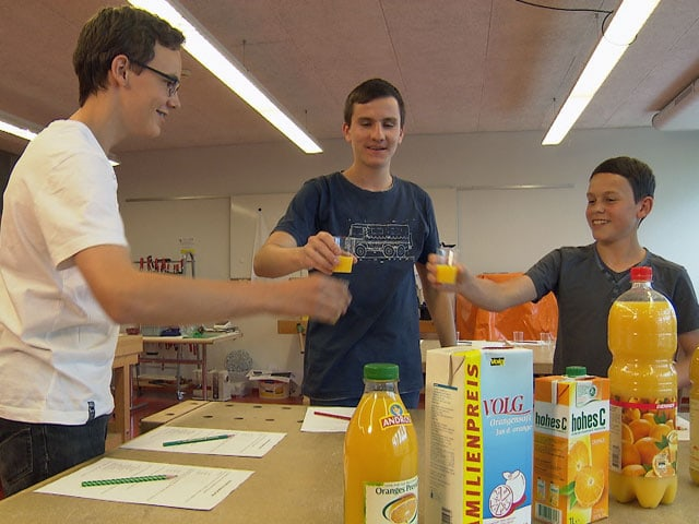 Drei Teenager in einem Schulzimmer stossen mit Orangensaft an.
