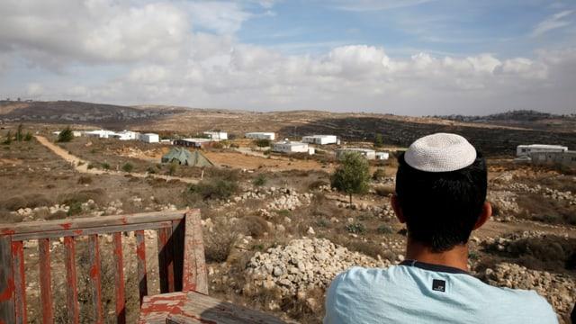 Ein Mann mit Kippa von hinten blickt über die Siedlung.