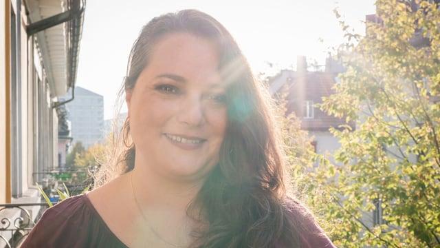 Porträt einer jungen Frau auf einem Balkon.