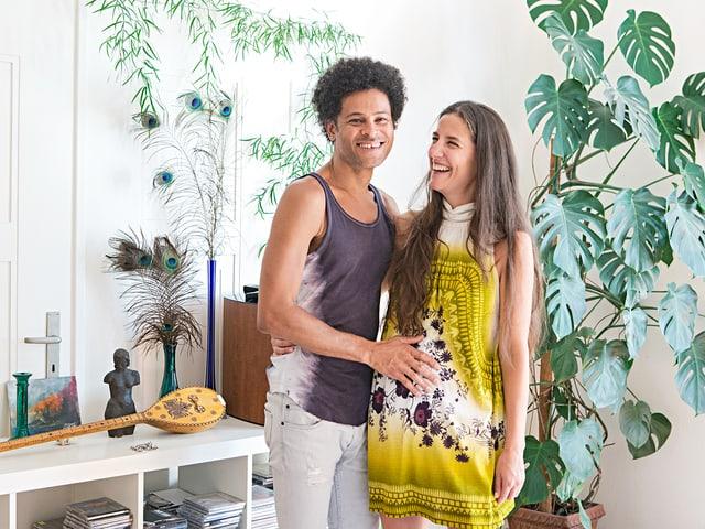 Walter Luiz Alves und Karen Pfister lachen. Eine Pflanze, ein Büchergestellt und Pfauenfedern sind im Hintergrund.