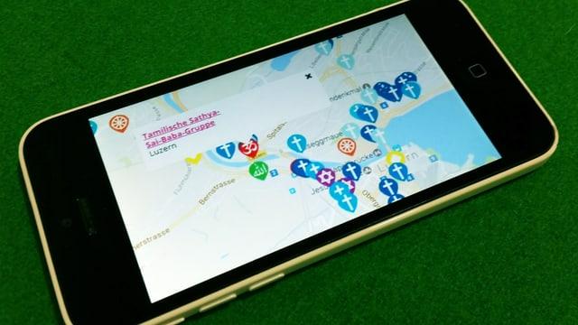 Handy auf dem eine Karte mit religiösen Symbolen zu sehen ist.