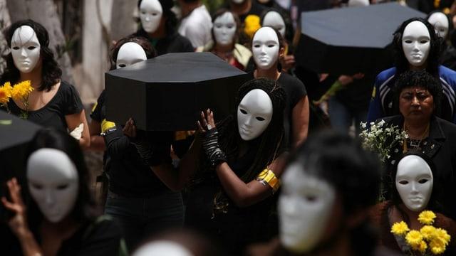Frauen mit weissen Masken und schwarz verhüllt tragen Särge