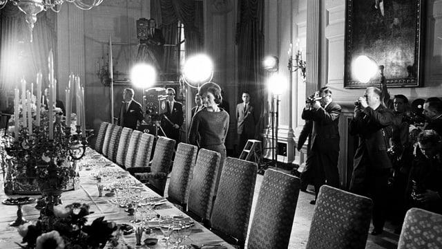 Jacqueline Kennedy im Weissen Haus an gedeckter Tafel, im Hintergrund Fotografen, Kameras, Filmlicht.