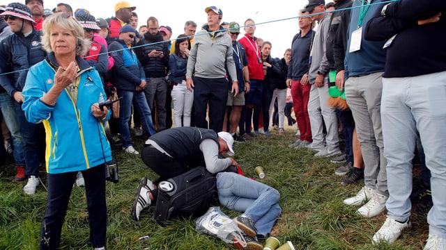 Eine Zuschauerin liegt getroffen am Boden.