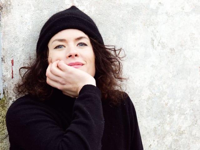 Eine Frau mit schwarzem Rollkragenpullover sitzt und lächelt in die Kamera.
