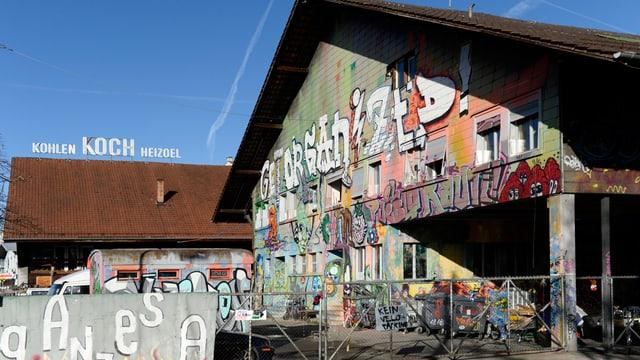 Ein Haus mit Schrägdach und vielen bunten Graffitis darauf. Vor dem Eingang stehen zahlreiche Fahrräder.