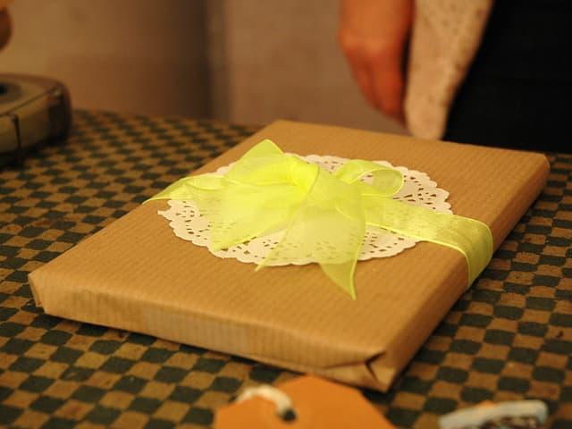 Geschenk in Packpapier mit einem weissen Tortenboden und einem gelben «Bändeli».