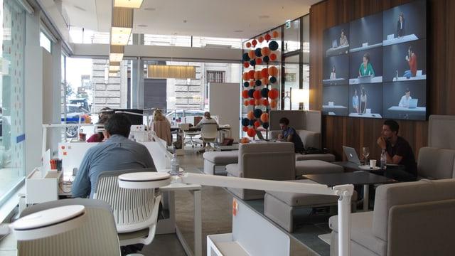 Ein Büroraum mit verschiedenen Tischen und Sofas. An den Plätzen sitzen Menschen vor Computern.