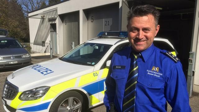 Ein Polizist steht vor einem Polizeiwagen.
