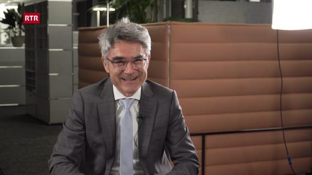 Mario Cavigelli ri en la camera en il zuler dal biro dal departement d'infrastructura, energia e mobilitad. Davos el in gond sort da sofa e cumpartement per duas persunas.