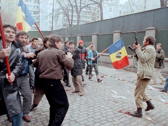 Ein Mann mit Maschinengewehr steht vor Demonstranten mit Flaggen.