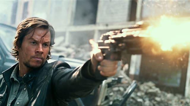 Der Filmheld schiesst mit einer futuristischen Pistole.