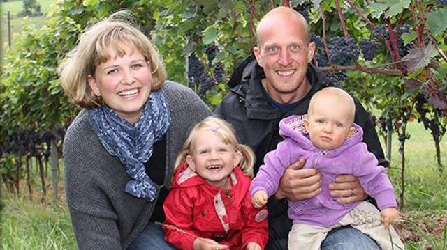 Familie mit zwei Kindern vor Rebstöcken.