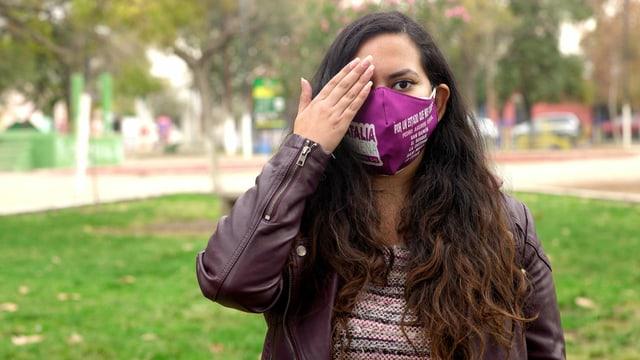Die chilenische Aktivistin Natalia Aravena mit einer Hand vor dem fehlenden Auge.