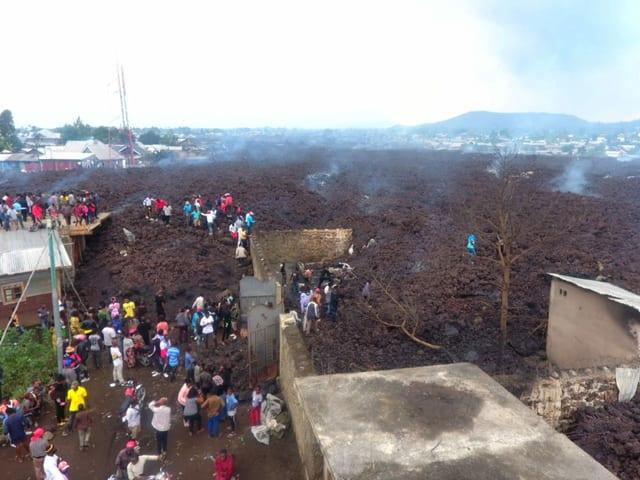 Luftaufnahme des Lavastroms in der Siedlung. Menschen klettern darauf rum.