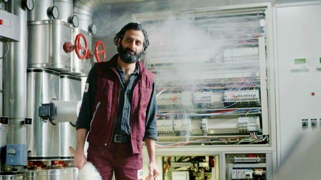 Ein Mann mit Bart steht in einem Raum mit vielen Kabeln und Schaltern.