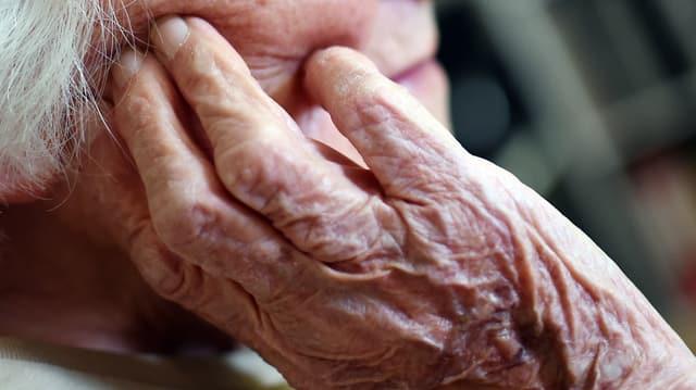Alte person, man sieht fast nur die Hände, auf welche sie ihr Gesicht stützt.