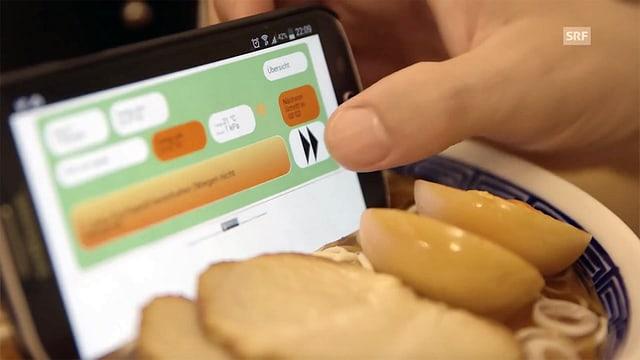 Ein Smartphone steckt in einer überteuerten asiatischen Suppen-Attrappe.