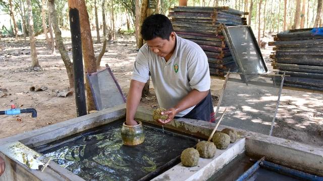 Ein Mann formt aus Elefantendunk Kugeln.