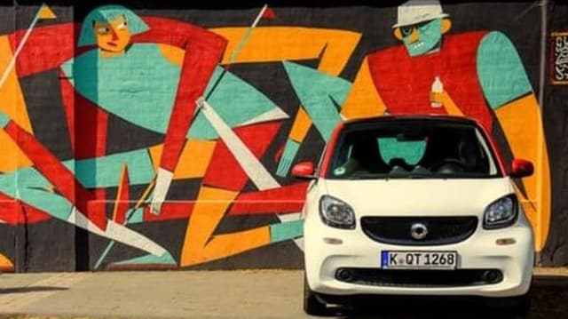 Ein Auto steht vor einer Street Art Wand.