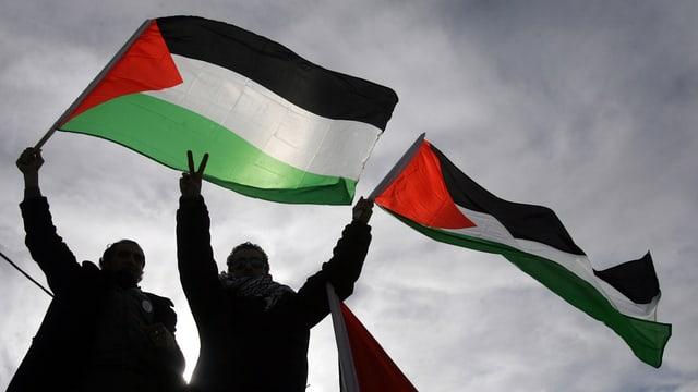 Zwei Palästinenser schwenken siegesbewusst ihre Flagge.