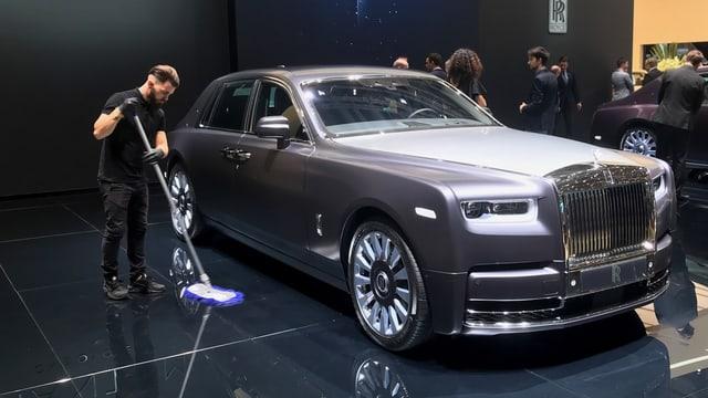 Ein Mann putzt neben einem Luxusauto den Boden.