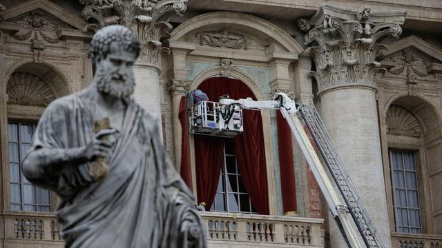 Im Vordergrund sieht man die Staue des Apostel Paulus vor dem Petersdom. Im Hintergrund montieren Menschen einen roten Vorhang vor die Balkontür.