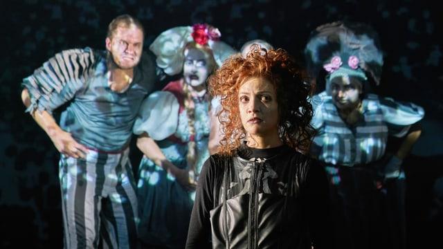 Eine Frau mit roten Haaren vor vier Gestalten.