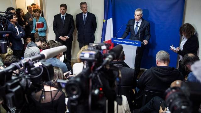 Il procuratur public Francois Molins è circumdà da schurnalists durant la conferenza da pressa en connex cun las attatgas da terror a Paris