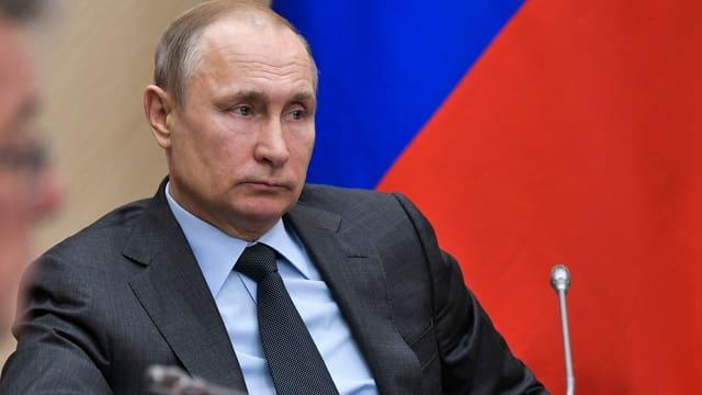 Wladimir Putin sitzt vor einer russischen Flagge, vor ihm ein Mikrofon.