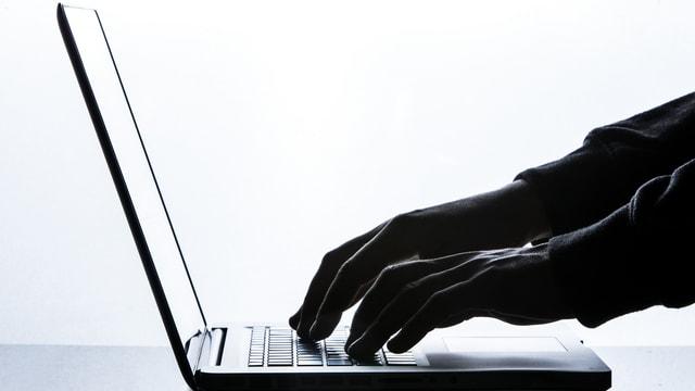 Ein Mann tippt auf eine Laptop-Tastatur