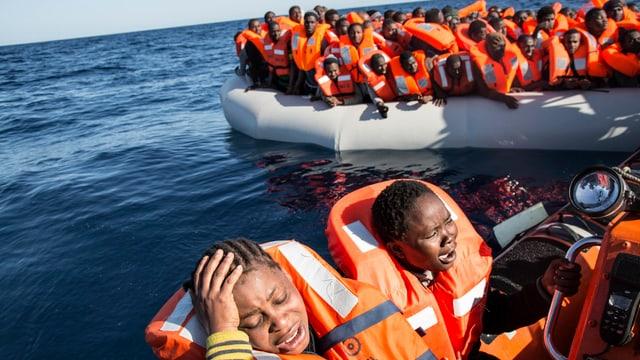 Menschen mit Schwimmwesten in Booten.