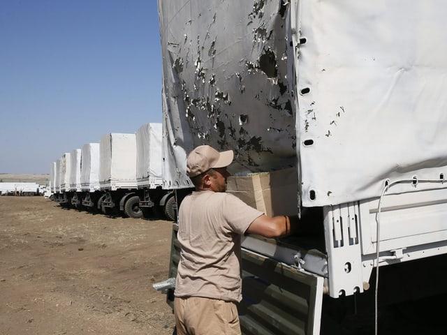Mann prüft Ladefläche eines Lastwagens.