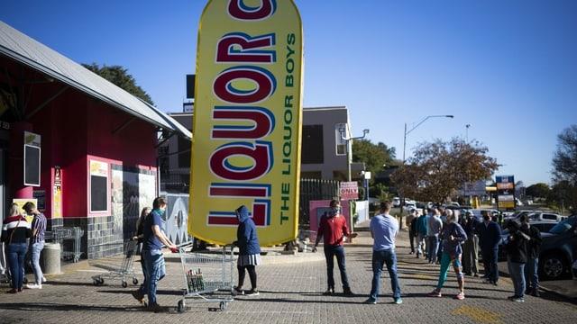Menschen stehen vor einem Alkohol Laden Schlange
