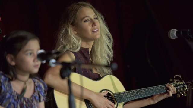 Blake Lively singend, mit blonden Haaren und Gitarre.