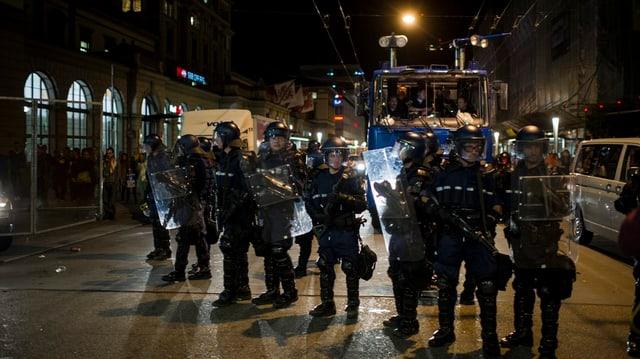 Bewaffnete Polizeibeamte nachts auf der Strasse, im Hintergrund ein Wasserwerfer-Fahrzeug