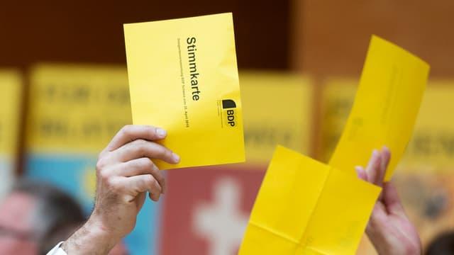 Ein Mann hält an der Versammlung der BDP eine gelbe Wahlkarte in die Höhe.