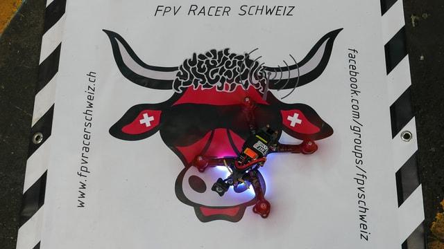Das Logo der FPV-Racer Schweiz (roter Stierkopf mit Schweizerkreuz in den Ohren und coller Sonnenbrille), darauf eine Racer-Drohne.