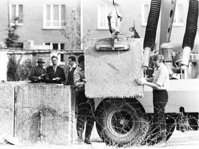 Bauarbeiter lassen mit einem Kran Steine für die Mauer herab.