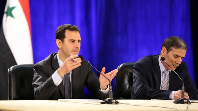 Zwei Männder an einem Tisch, der eine spricht gestikulierend.